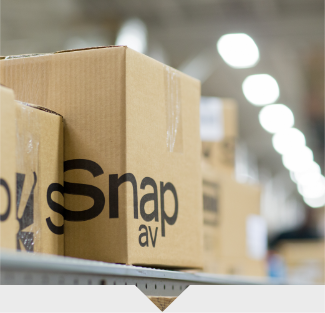 SnapAV boxes sitting on a conveyer belt