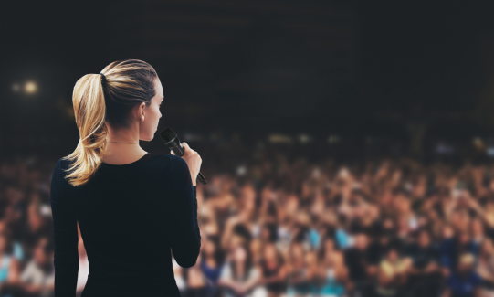 Mobile image of a female speaking to a crowd using a microphone