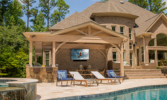 TV mounted on the back wall of a house by the pool