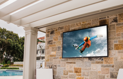 Sunbrite television installed in wall beside a pool