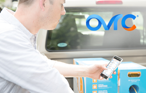 Dealer leaning over back of truck holding smart phone and OvrC logo at the top of image