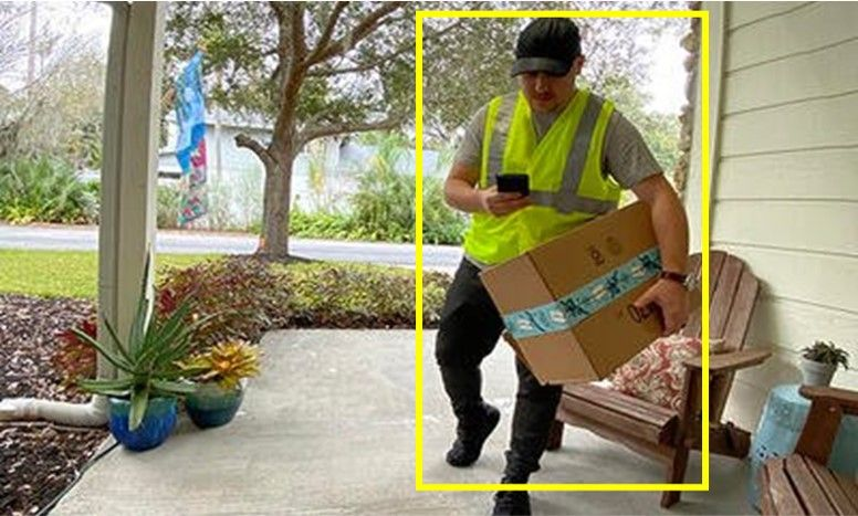 Delivery person dropping off box at residence