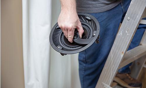 Installer holding speaker during install while standing on a ladder