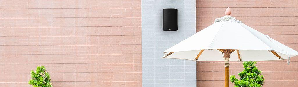 Outdoor scene by brick building with umbrella dn Venura speaker mounted on exterior