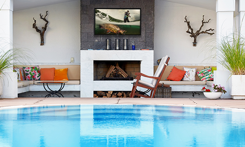Outdoor pool with TV installed in covered porch